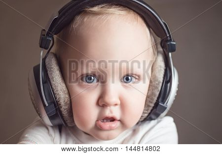 Funny baby in big gray headphones listening to music