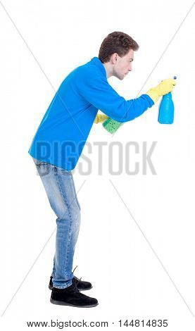 side view of a cleaner man in gloves with sponge and detergent. Curly boy in a warm blue sweater in the process of cleaning a side view.