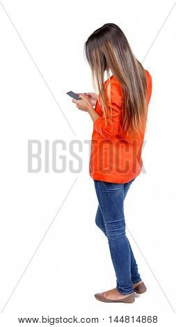 back view of standing young beautiful woman using a mobile phone or tablet computer. girl in a red jacket stands sideways and dials the number.