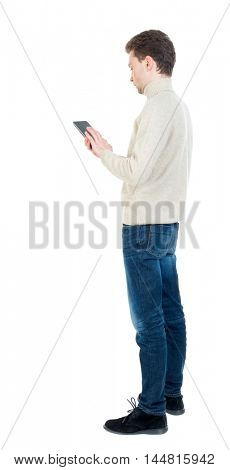 back view of business man uses mobile phone. Curly short-haired man in a woolen white jacket standing sideways and leafing through an e-book.