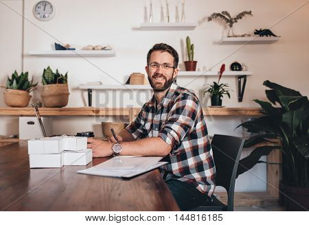 Portrait of a young entrepreneur sitting at a table at home using a laptop next to paperwork and packages ready for delivery to customers