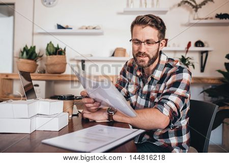 Young entrepreneur sitting at a table at home using a laptop and reading paperwork while preparing packages for delivery to customers
