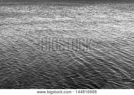 the big textured water surface with ripples for an abstract natural background of dark gray or black color