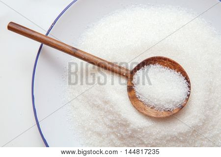 Close-up of granulated sugar in spoon and sugar pile.