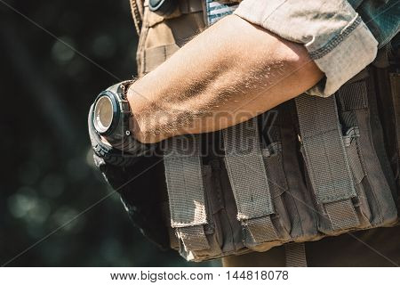 Male soldier wearing a bulletproof vest and a shirt with short sleeves. On hand watches.