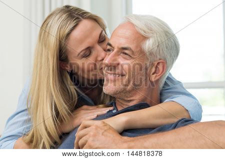 Senior woman embracing her husband from behind. Close up face of mature woman kissing man on cheek in living room. Portrait of a loving wife kissing senior man.