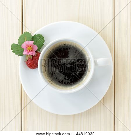 Black coffee with decoration of berry flower and leaf strawberries on a pine wooden background top view / coffee with strawberries