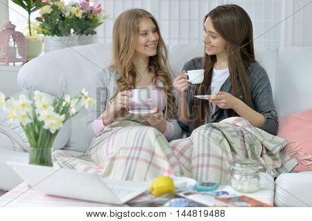 happy friends  drinking coffee or tea  on  couch at home