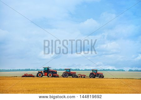 Summer day three tractor with plow standing on the sloping wheat field before the beginning of the work. Land preparation before planting.