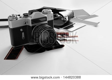 Vintage photo camera with photos on white table