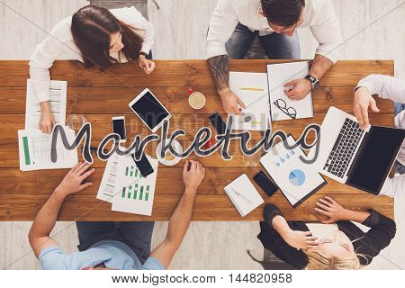Marketing meeting. Group of business people work in office, top view of wood table with mobile phones, laptop, tablet and documents papers with diagram. Men and women team have brainstorm discussion.