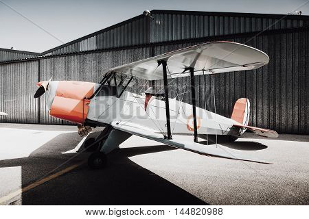 Old vintage plane parked at the aerodrome. Side view.