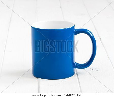 simple blue cup with white inside on white wooden table