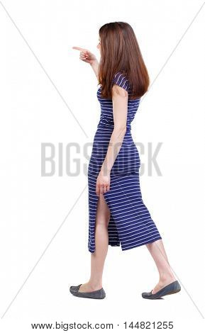 back view of pointing walking woman. brunette in a blue striped dress goes on the side pointing forward.