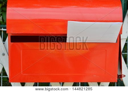 white envelope in red post box on home fence