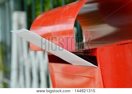 white envelope in red mail box on home fence