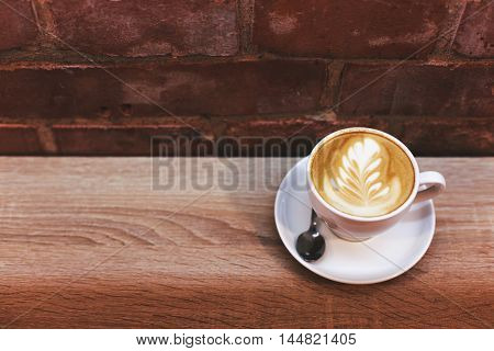 Cappuccino on the table near brick wall. Lattee art.