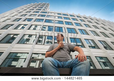 Bottom view middle age man portrait with coffee cup in the city