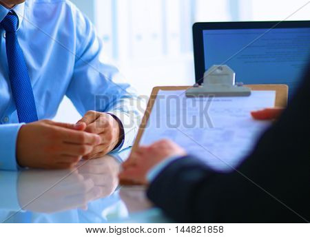 Businesspeople sitting on the desk on office .