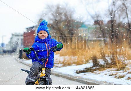 happy cute little boy riding bike in winter, kids sport