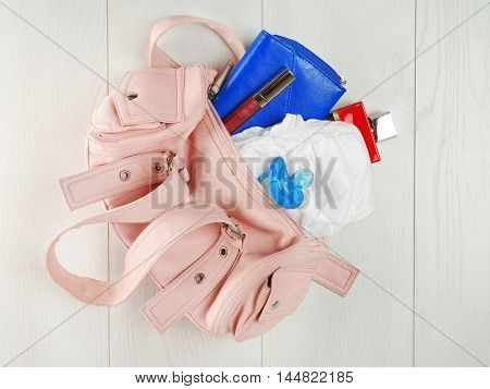 Mothers bag with accessories on wooden background