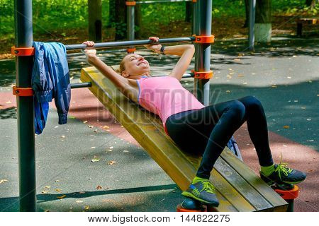 Young slim woman doing workout on training ground in a park