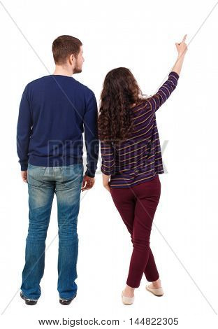 young couple pointing at wal Back view (woman and man). Swarthy girl and a bearded man looking up.