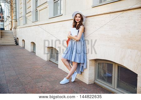 Cheerful cute young woman standing on the street and holding blank magazines