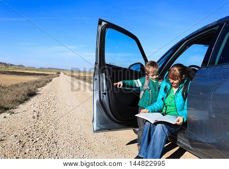 family travel - mother and little son looking at map on road to mountains
