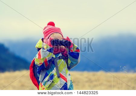 family travel- cute little girl with binoculars exploring winter mountains