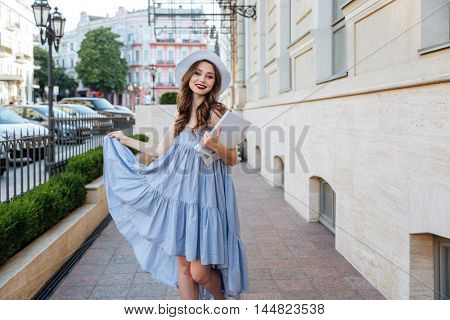Happy pretty young woman in hat and blue dress with blank magazines in the city
