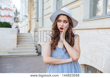 Portrait of a sad cute brunette girl looking away outdoors