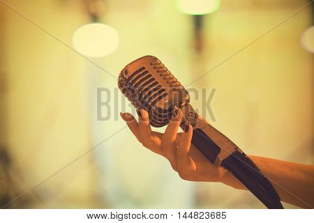 Female hand with vintage  microphone on colorful lights background