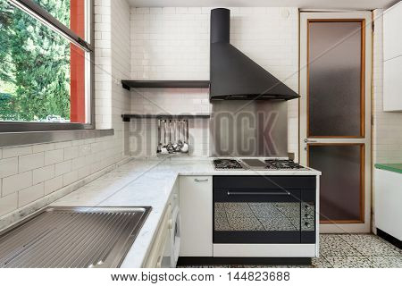 Old domestic kitchen of an apartment, gas stove with hood