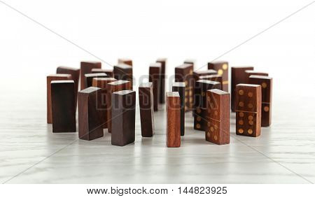 Circle of dominoes standing on light wooden background
