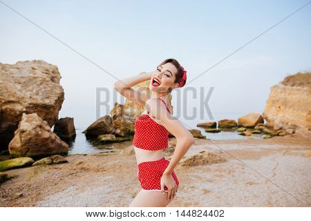 Young beautiful pin up girl in red swimsuit posing while standing at the beach