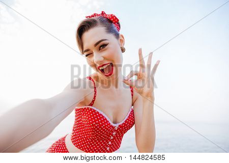 Happy pretty pinup girl in red swimsuit winking and showing okay sign while standing at the beach