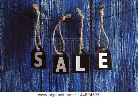 Sale labels hanging on wooden background