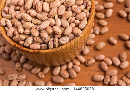 Carioca Beans into a bowl over a wooden table