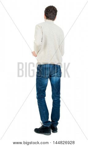 Back view of man . Curly short-haired man in a woolen white jacket thoughtfully looking forward.