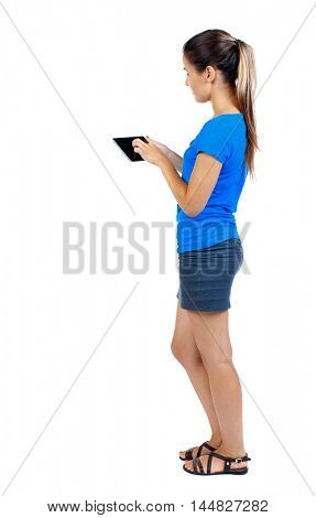 back view of standing young beautiful woman using a mobile phone or tablet computer. girl watching. girl in a short skirt and a blue shirt stands sideways and manages a finger on the tablet.