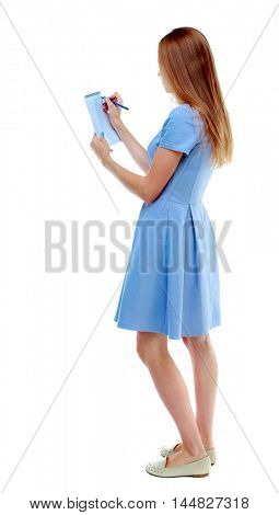 back view of stands woman takes notes in a notebook. Isolated over white background. Skinny girl in a blue dress and writing in a notebook.