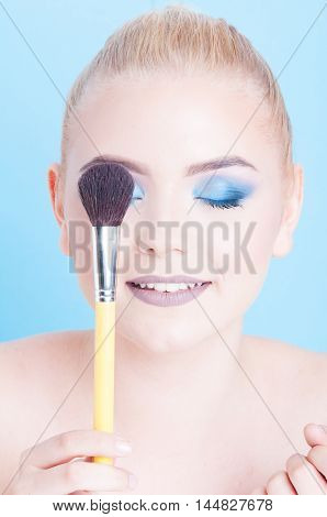 Woman Covering Eye With Professional Make-up Brush