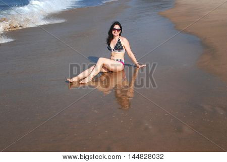 Happy beautiful girl in a bikini is sitting on the beach at the water's edge and she is mirrored in the water on the wet sand