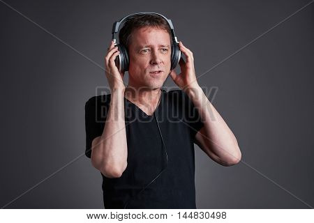 A middle age listening some music on the headphone and singing