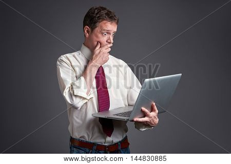 A middle age man standing and using a laptop and feeling scared.