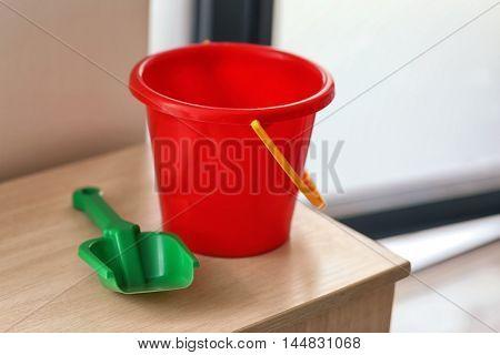 Children bucket and shovel on table