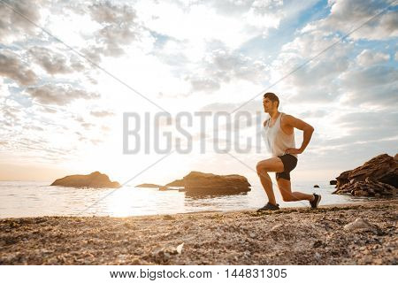 Young healthy man athlete doing squats at the beach at sunset