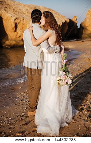 Back view of a romantic happy married couple standing at the beach