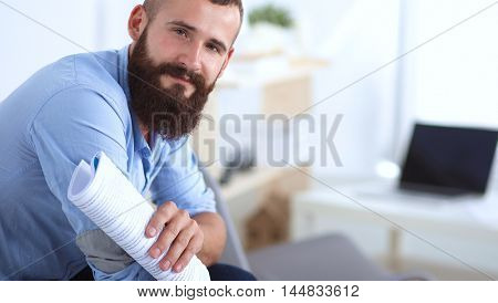 Young businessman sitting on chair with book in office